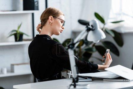 Schöne Geschäftsfrau in schwarzer Kleidung und Brille, die aufs Smartphone schaut