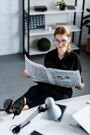 Photo for Beautiful businesswoman in black clothes and glasses sitting at table and reading newspaper - Royalty Free Image