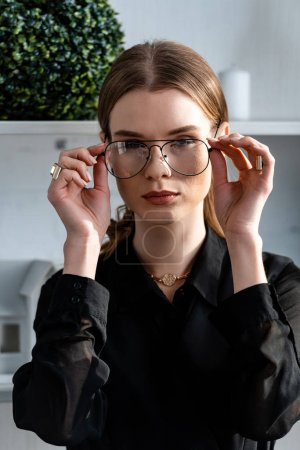 Photo for Portrait of beautiful woman in black putting on glasses - Royalty Free Image