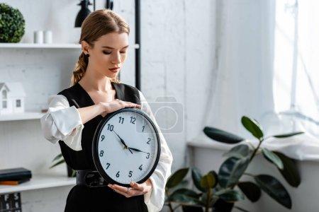 femme attrayante dans l'usure formelle tenant horloge sur le lieu de travail