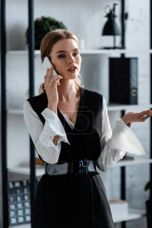 businesswoman in formal wear gesturing and talking on smartphone in office