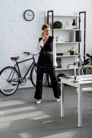 Photo pour Femme d'affaires en tenue formelle parlant sur smartphone dans un bureau moderne - image libre de droit
