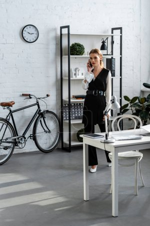 Photo pour Femme d'affaires grave en vêtements parler sur smartphone dans le bureau moderne - image libre de droit