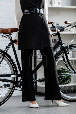 Photo pour Vue recadrée de la femme en noir tenue formelle avec vélo - image libre de droit