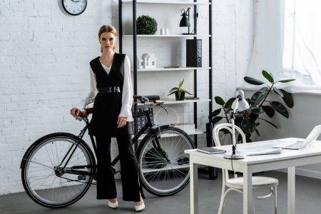 Photo pour Femme d'affaires grave en tenues à vélo au bureau moderne - image libre de droit