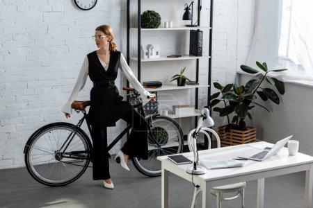 Photo pour Femme d'affaires en tenue formelle avec vélo au bureau moderne - image libre de droit