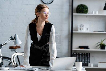 femme d'affaires en tenue de cérémonie et lunettes debout près du bureau de l'ordinateur sur le lieu de travail et regardant loin