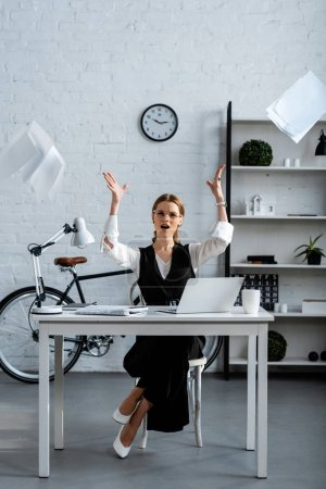 Photo for Dissatisfied businesswoman in formal wear sitting at desk, gesturing with hands and throwing documents in air at workplace - Royalty Free Image