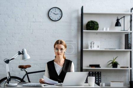 Foto de Mujer de negocios seria en ropa formal sentada en el escritorio de la computadora con documentos en el lugar de trabajo - Imagen libre de derechos