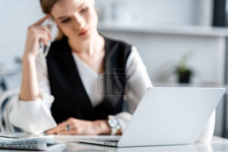 Photo pour Foyer sélectif de l'ordinateur portable avec une femme d'affaires en tenue formelle assis sur le lieu de travail sur fond - image libre de droit