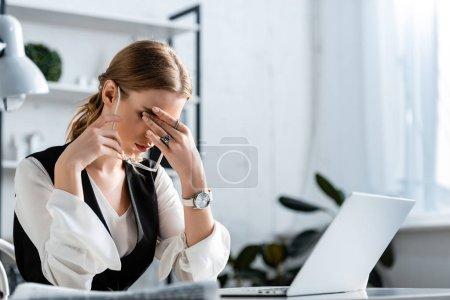 femme d'affaires en tenue formelle assise au bureau de l'ordinateur, touchant le front et souffrant de maux de tête sur le lieu de travail