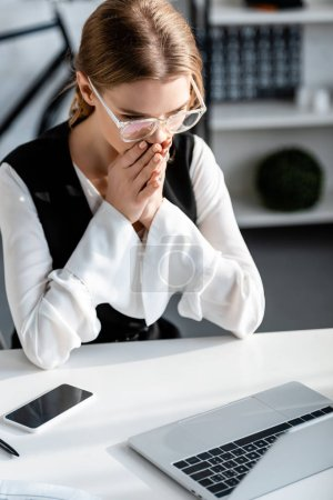 foyer sélectif de femme d'affaires choquée en tenue formelle avec les mains pliées assis au bureau de l'ordinateur sur le lieu de travail