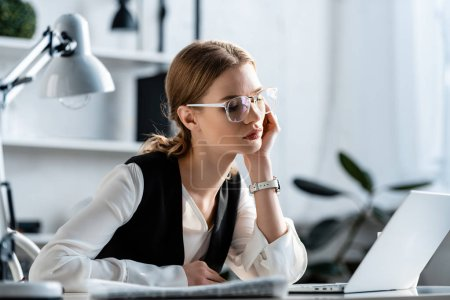 belle femme d'affaires en tenue formelle et lunettes assis au bureau de l'ordinateur sur le lieu de travail