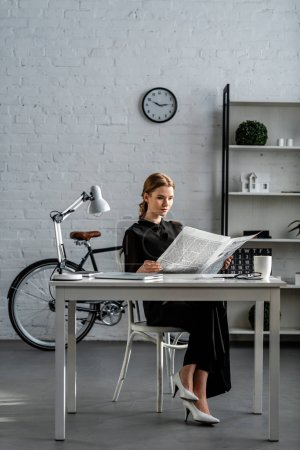 Photo for Businesswoman in black formal wear sitting at desk and reading newspaper in office - Royalty Free Image