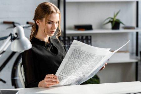 Photo pour Femme d'affaires concentrée en noir vêtements formels assis au bureau et lire le journal sur le lieu de travail - image libre de droit