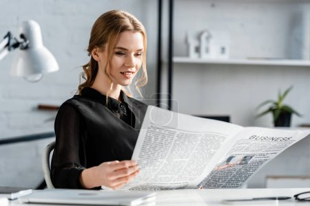 Photo for Smiling businesswoman in black formal wear sitting at desk and reading newspaper at workplace - Royalty Free Image