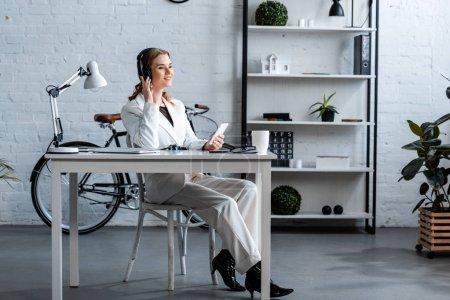 Photo pour Femme d'affaires souriante dans les écouteurs assis au bureau et en utilisant smartphone dans le bureau - image libre de droit