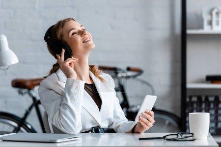 Photo pour Femme d'affaires riante dans les écouteurs assis au bureau et en utilisant smartphone sur le lieu de travail - image libre de droit