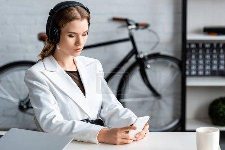 Photo pour Femme d'affaires concentrée dans les écouteurs assis au bureau et en utilisant smartphone sur le lieu de travail - image libre de droit