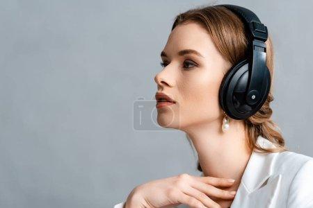 Photo pour Portrait de la belle femme écoutant de la musique au casque et à la recherche de suite avec espace copie - image libre de droit