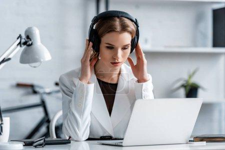 femme d'affaires en casque et vêtements formels assis au bureau de l'ordinateur sur le lieu de travail
