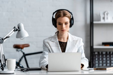 Photo for Serious businesswoman in headphones sitting at computer desk at workplace - Royalty Free Image