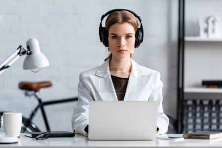 Photo pour Femme d'affaires grave dans les écouteurs, assis au bureau de l'ordinateur au lieu de travail - image libre de droit