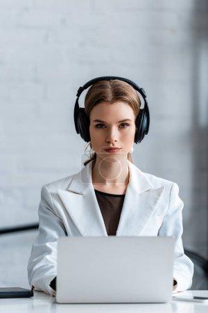 femme d'affaires concentrée dans les écouteurs assis au bureau informatique sur le lieu de travail