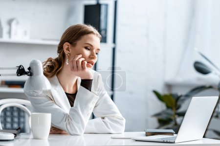 Photo for Tired businesswoman in white formal wear touching chin while sitting at computer desk at workplace - Royalty Free Image