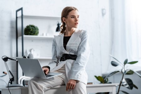 stylish businesswoman in white formal wear sitting on desk with laptop at workplace and looking away