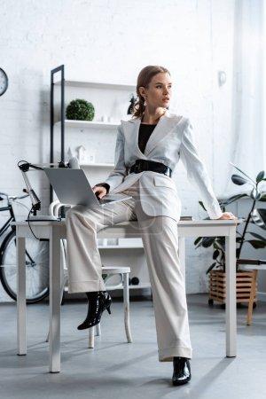 Photo pour Femme d'affaires en vêtements blancs assis sur le bureau avec ordinateur portable au bureau et à la recherche. - image libre de droit