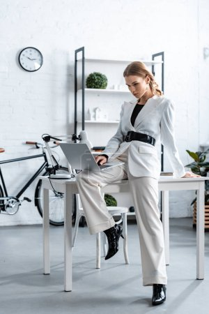 Photo for Stylish businesswoman in white formal wear sitting on desk and using laptop at workplace - Royalty Free Image