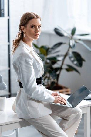 schöne Geschäftsfrau in weißer Festkleidung sitzt am Schreibtisch, schaut in die Kamera und benutzt Laptop am Arbeitsplatz