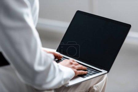 Photo pour Vue recadrée de femme à l'aide d'ordinateur portable avec écran blanc - image libre de droit