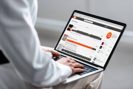 cropped view of woman using laptop with soundcloud website on screen