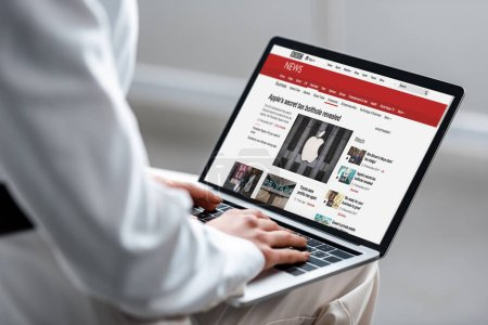 Photo for Cropped view of woman using laptop with bbc news website on screen - Royalty Free Image