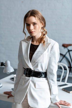 schöne stilvolle Frau in weißer formaler Kleidung, die in die Kamera schaut