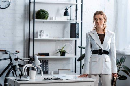 Photo pour Femme d'affaires concentrée en vêtements regarder loin dans l'intérieur bureau moderne - image libre de droit