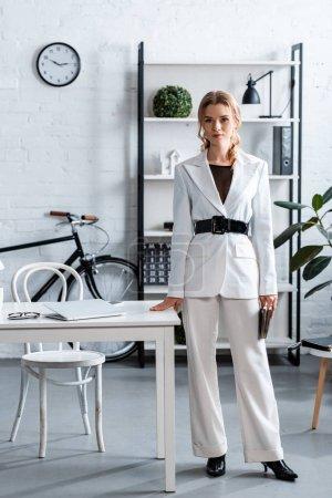 Photo pour Femme d'affaires sérieux en regardant la caméra à l'intérieur de bureau moderne blanc vêtements - image libre de droit