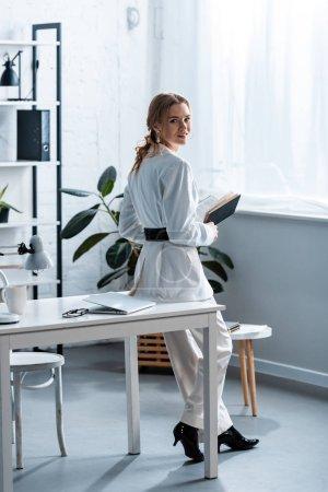 Photo pour Femme d'affaires souriante en tenue formelle tenant un carnet et regardant la caméra dans le bureau - image libre de droit