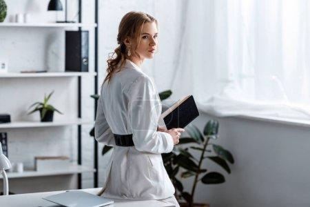 fokussierte Geschäftsfrau in offizieller Kleidung hält Notizbuch im Büro