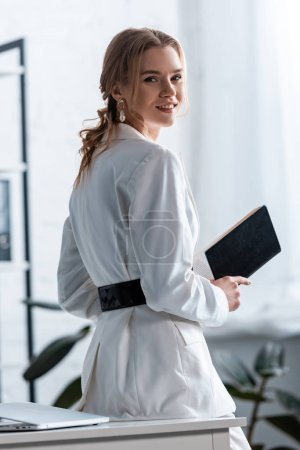 smiling businesswoman in formal wear holding notebook and looking at camera at workplace