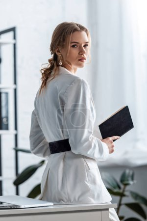 beautiful businesswoman in formal wear holding notebook and looking at camera at workplace