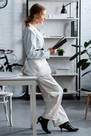 Photo pour Femme d'affaires élégante en tenue formelle assis sur le bureau et le cahier de lecture sur le lieu de travail - image libre de droit