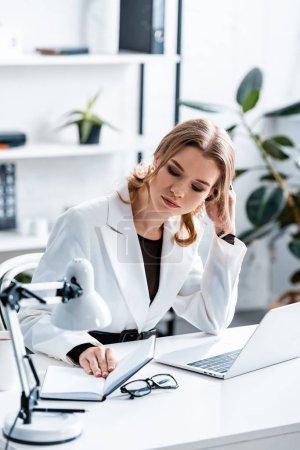 femme d'affaires concentrée en tenue de cérémonie assis au bureau de l'ordinateur et regardant le carnet dans le bureau