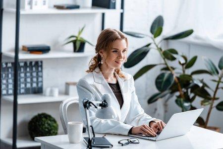 Photo pour Sourire de femme d'affaires en tenues assis au bureau et à l'aide de portable au milieu de travail - image libre de droit