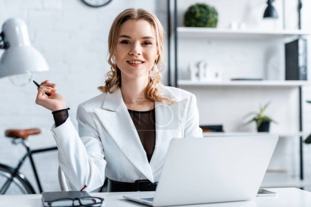 Photo for Smiling businesswoman in formal wear sitting at desk, holding pen and looking at camera at workplace - Royalty Free Image