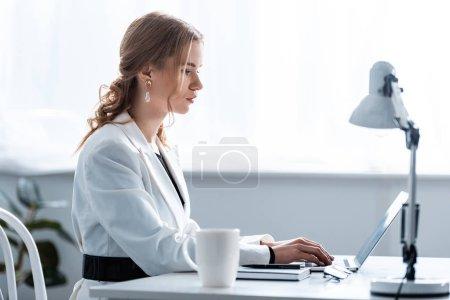 Photo pour Femme d'affaires concentrée en tenue formelle assise au bureau et tapant sur ordinateur portable sur le lieu de travail - image libre de droit