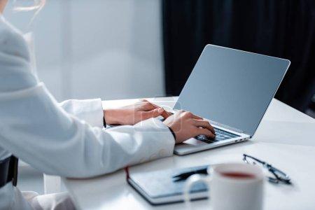 Photo pour Vue recadrée de femme à l'aide d'ordinateur portable avec écran blanc au comptoir de bureau à bureau - image libre de droit