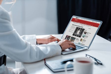 Photo for Cropped view of woman using laptop with bbc news  website on screen at office desk - Royalty Free Image